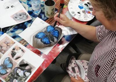 Podczas zajęć aktywizujących uczestnicy PAS-Z w Ochli przygotowali dekoracje ogrodu – malowane kamienie.